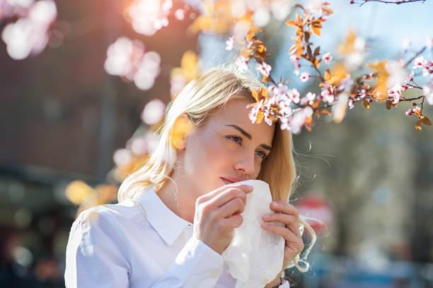 woman sneezing in the blossoming garden - pyłek zdjęcia i obrazy z banku zdjęć