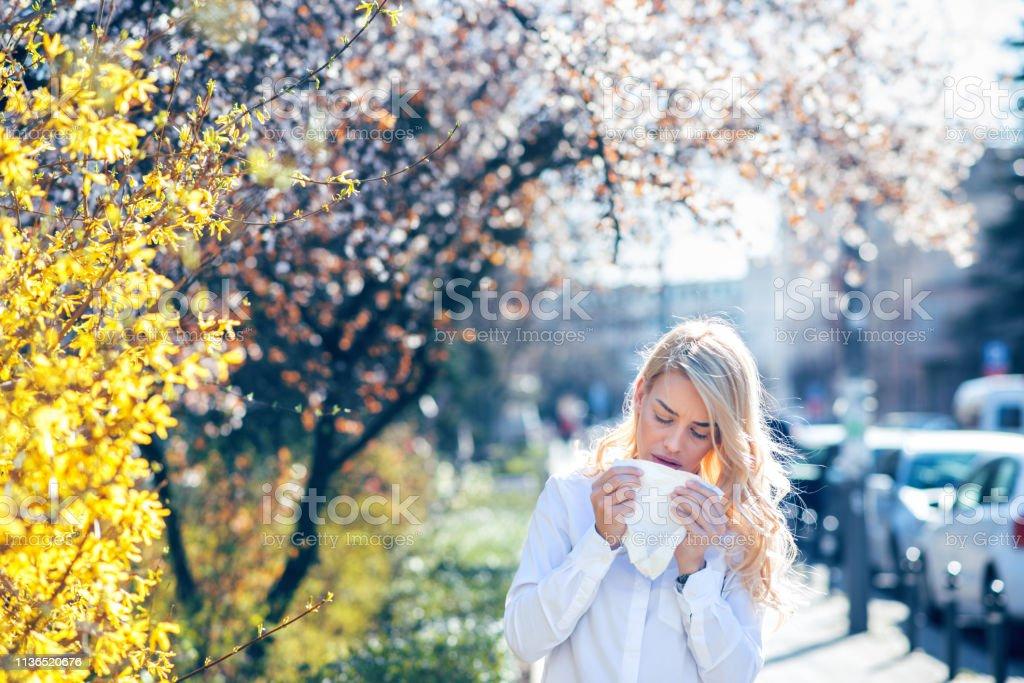 Vrouw niezen in de bloeiende tuin - Royalty-free Afweer Stockfoto