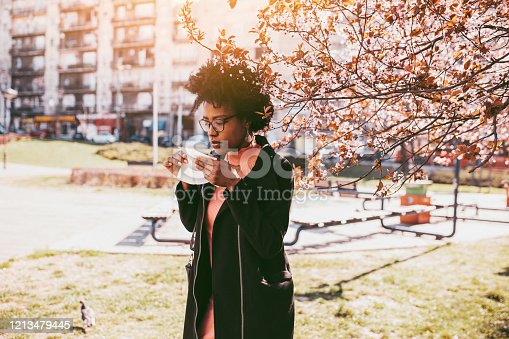 Attractive young African American woman coughing and sneezing outdoors. Sick people allergy or virus influenca concept.