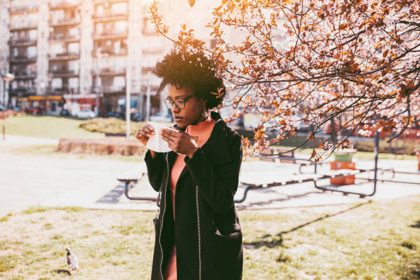 Woman sneezing in the blossoming garden Attractive young African American woman coughing and sneezing outdoors. Sick people allergy or virus influenca concept. allergy stock pictures, royalty-free photos & images