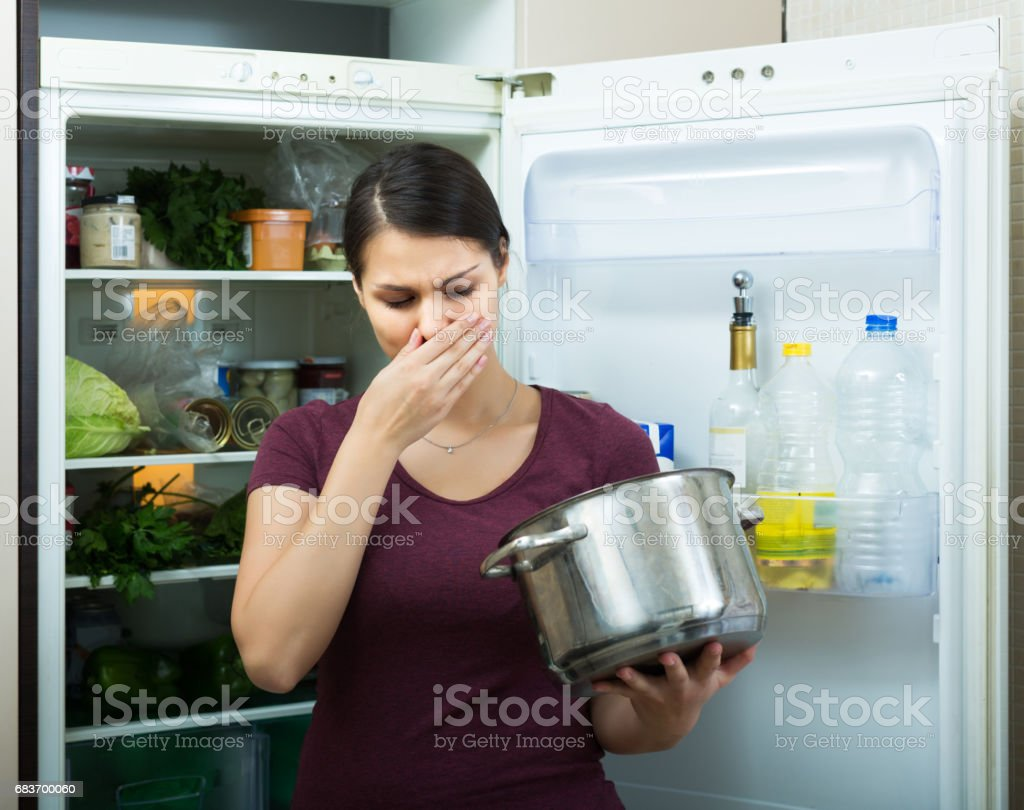 Woman sniffing at foul food stock photo