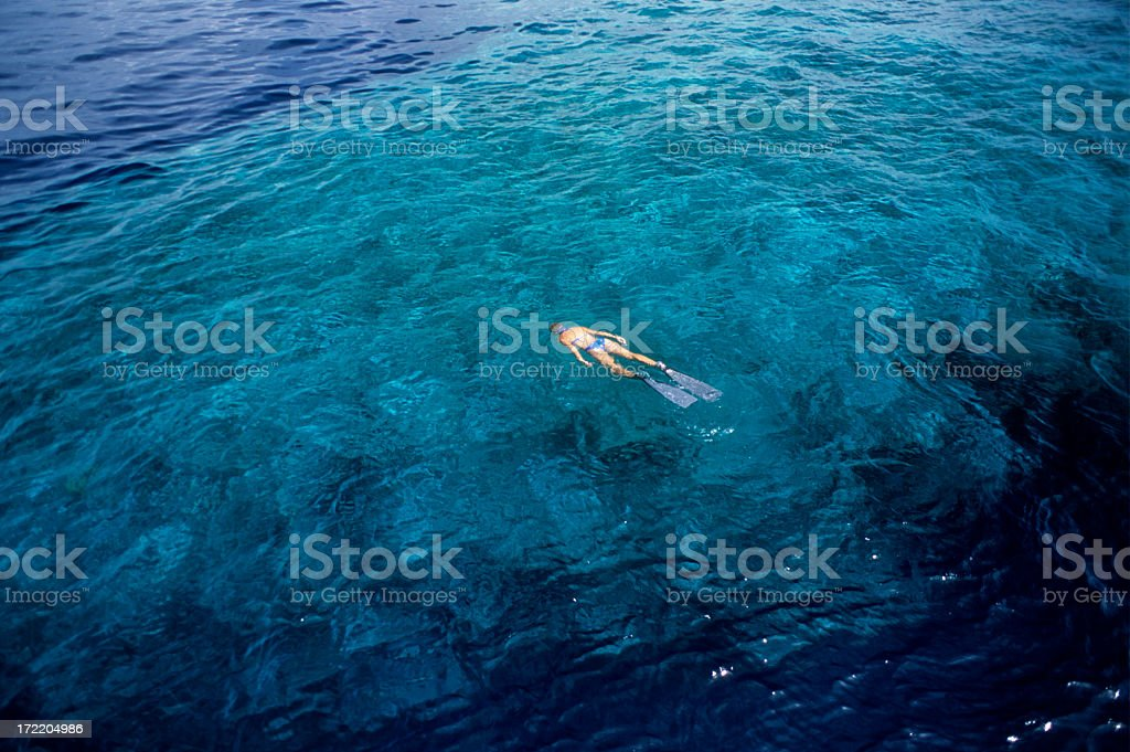 Woman snorkeling in a deep blue ocean royalty-free stock photo