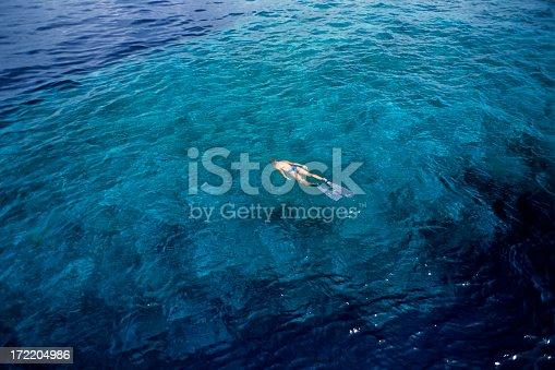 istock Woman snorkeling in a deep blue ocean 172204986