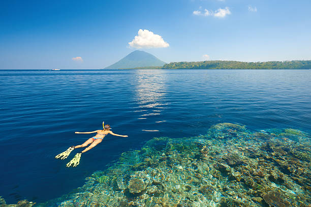 Woman snorkeling in clear tropical waters on background of island Young woman in swimsuit snorkeling in blue and transparent tropical sea on a background volcano Manado Tua.  North Sulawesi, Indonesia. manado stock pictures, royalty-free photos & images