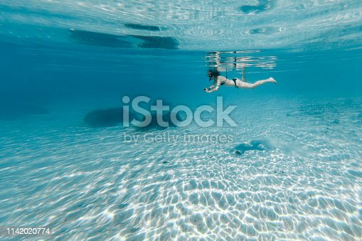 Woman snorkeling in crystal clear water in Bora Bora taking picture underwater
