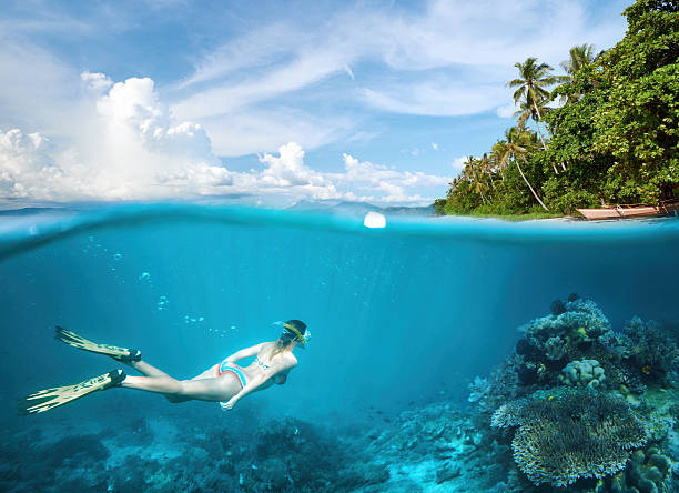 Woman snorkeling in tropical waters in near of exotic island stock photo