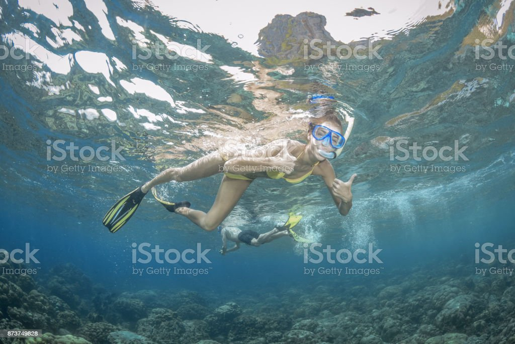 Woman snorkeling over a reef, Gesturing Thumbs Up stock photo