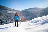 happy smiling sporty 45 years old woman in winter sport outdoor clothes snowshoeing in deep fresh snow on cold sunny day in beautiful winterly landscape with snowcovered trees and sunshine