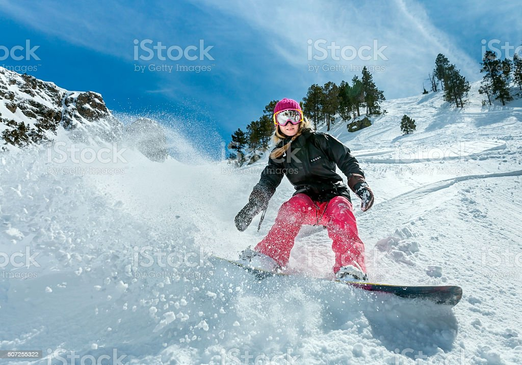 Woman snowboarder in motion in mountains stock photo