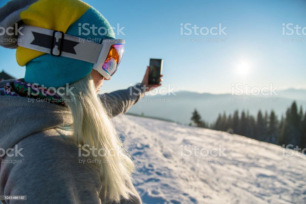Woman snowboarder relaxing after snowboarding, taking photos of...