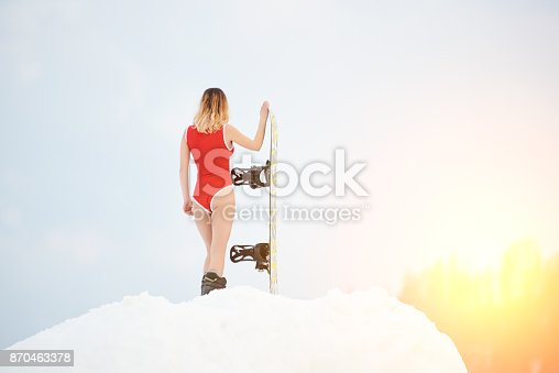 istock Woman snowboarder with snowboard on snowy slope at winter ski resort 870463378