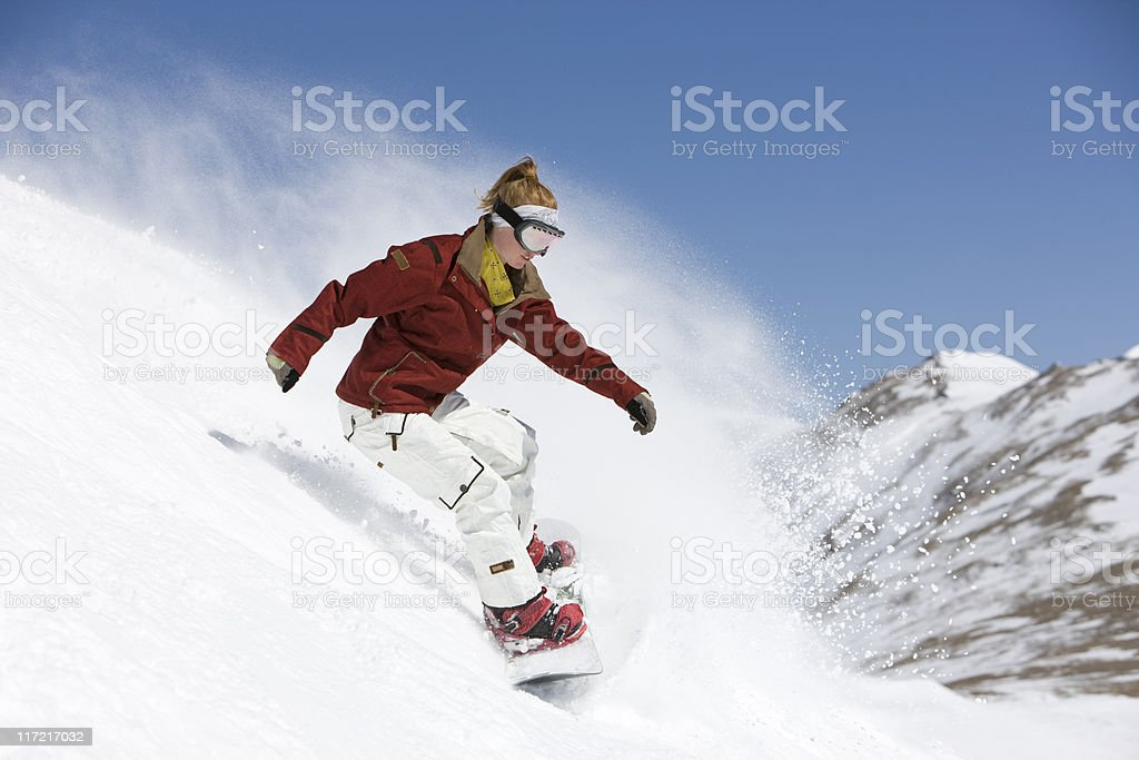 Woman Snowboarding Against A Blue Sky royalty-free stock photo