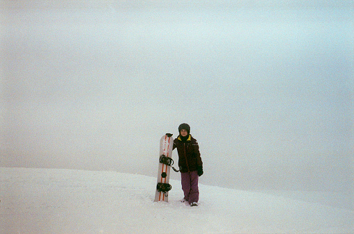 Woman snowboarding in mountains. Camera film