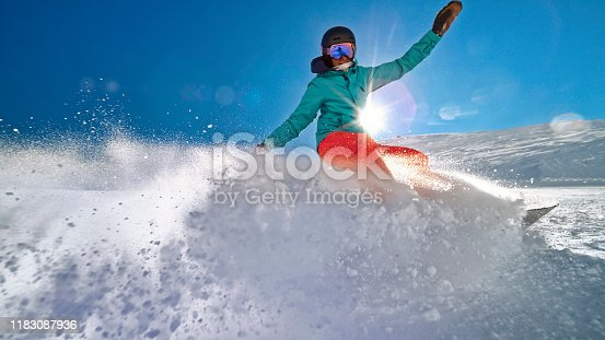 Woman snowboarding on mountain slope against sky.