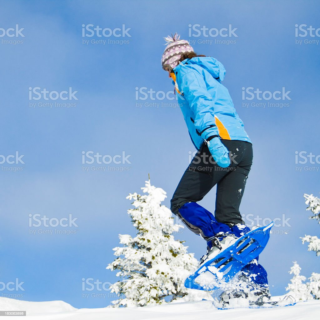 A woman snowshoeing outdoors at wintertime royalty-free stock photo