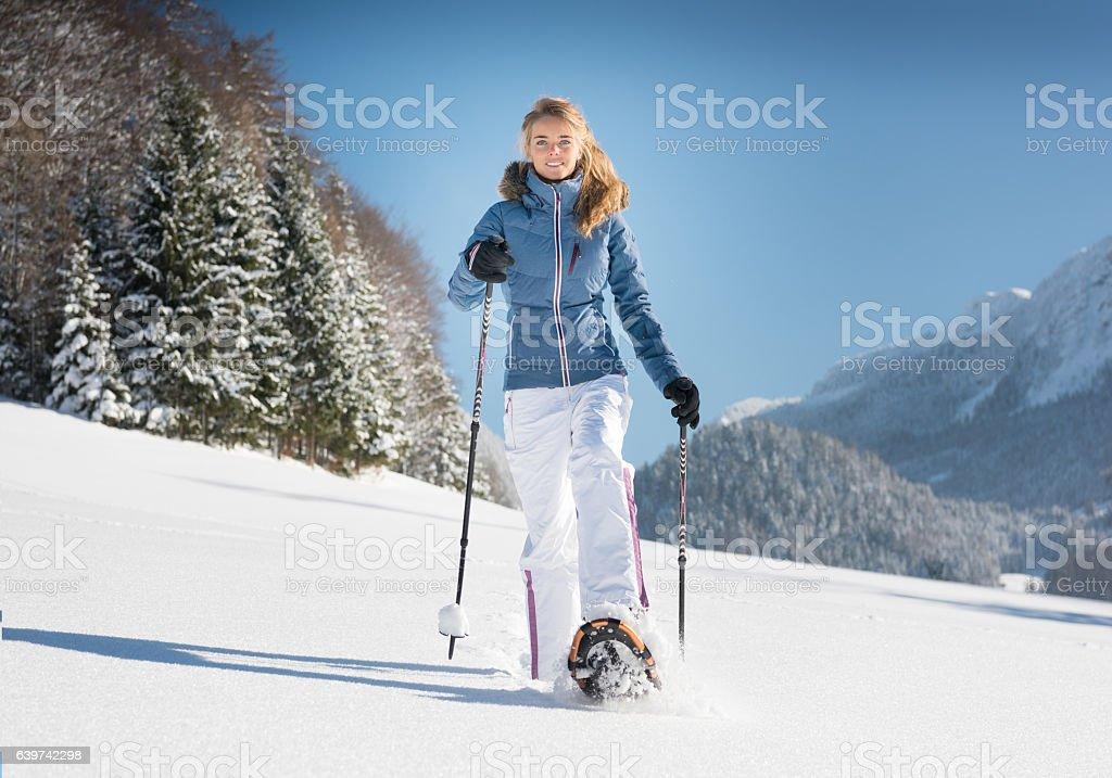 Woman Snowshoeing through a Winter Wonderland, Austrian Alps stock photo