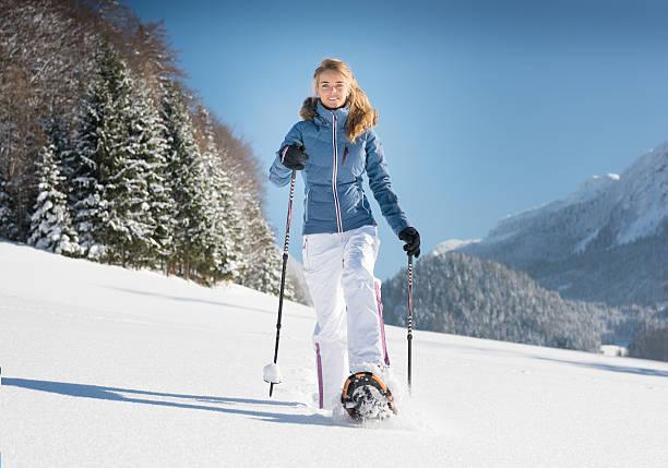 woman snowshoeing through a winter wonderland, austrian alps - raquette photos et images de collection