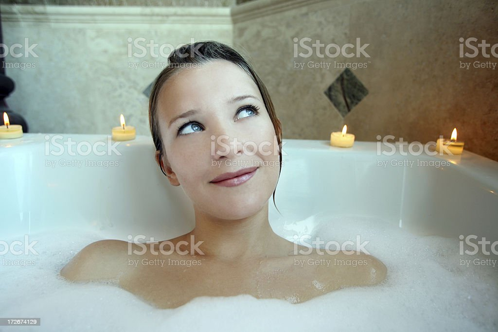 Woman soaking in Relaxing Bubble Bath Tub and Thinking royalty-free stock photo