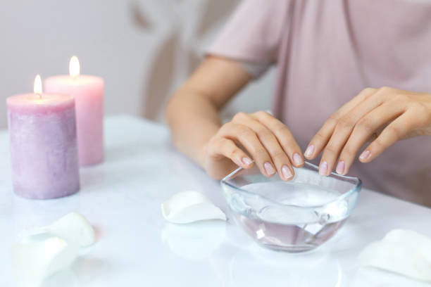 woman soaking natural nails in bowl full of water. nail care - cuticle stock pictures, royalty-free photos & images