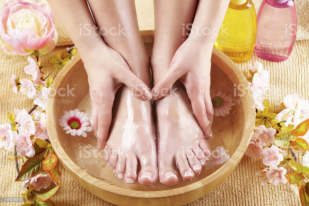 A woman soaks her feet in a bamboo bowl of water stock photo