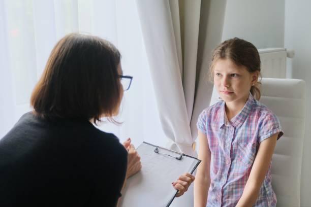 Mujer trabajadora social psicóloga hablando con niña en el cargo - foto de stock