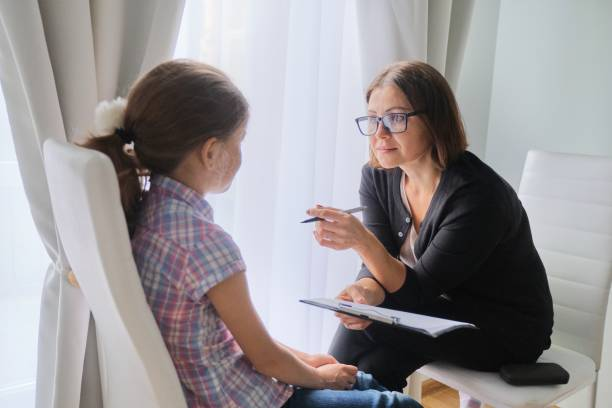 Kadın sosyal hizmet görevlisi kızla konuşuyor. Çocuk psikolojisi, ruh sağlığı stok fotoğrafı