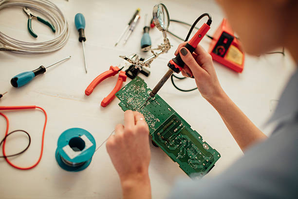 Woman Soldering a circuit board in her office. Close up of female engineers hands using soldering iron in her office. Testing and fixing a circuit board. soldering iron stock pictures, royalty-free photos & images
