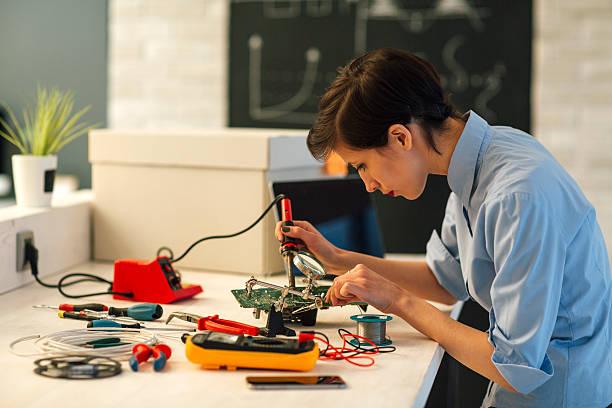 Una mujer de soldadura en placa de circuito tecnología en su oficina. - foto de stock