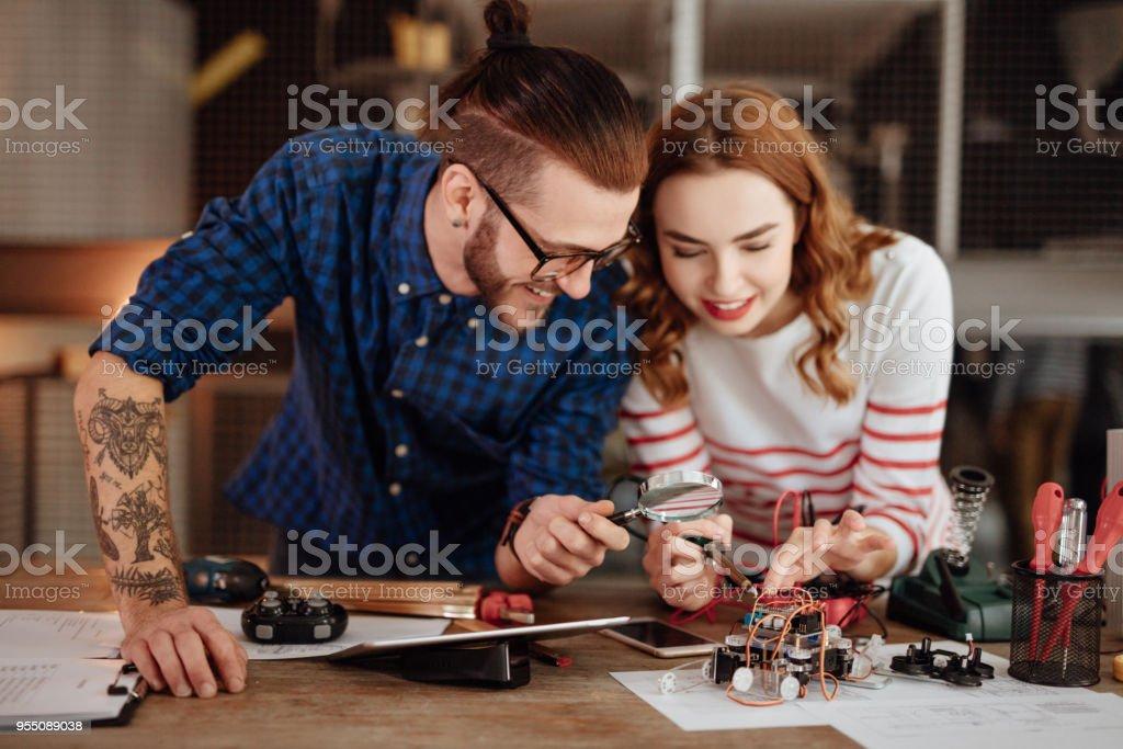 Löten einer Leiterplatte in Tech Büro mit Hilfe von ihren Kollegen Frau – Foto