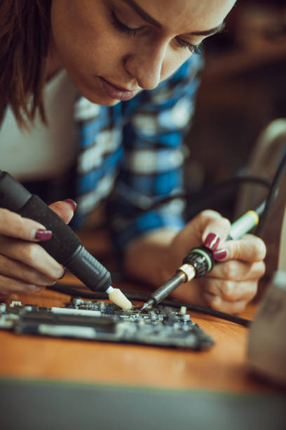 Woman Soldering a circuit board Woman Soldering a circuit board soldering iron stock pictures, royalty-free photos & images