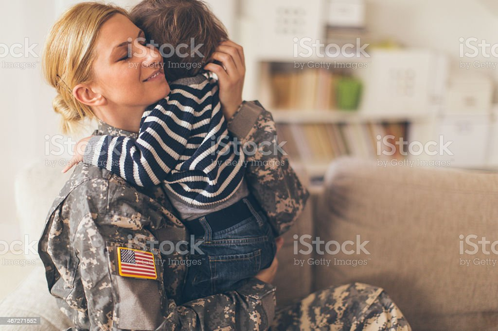 Woman soldier hugging her son stock photo