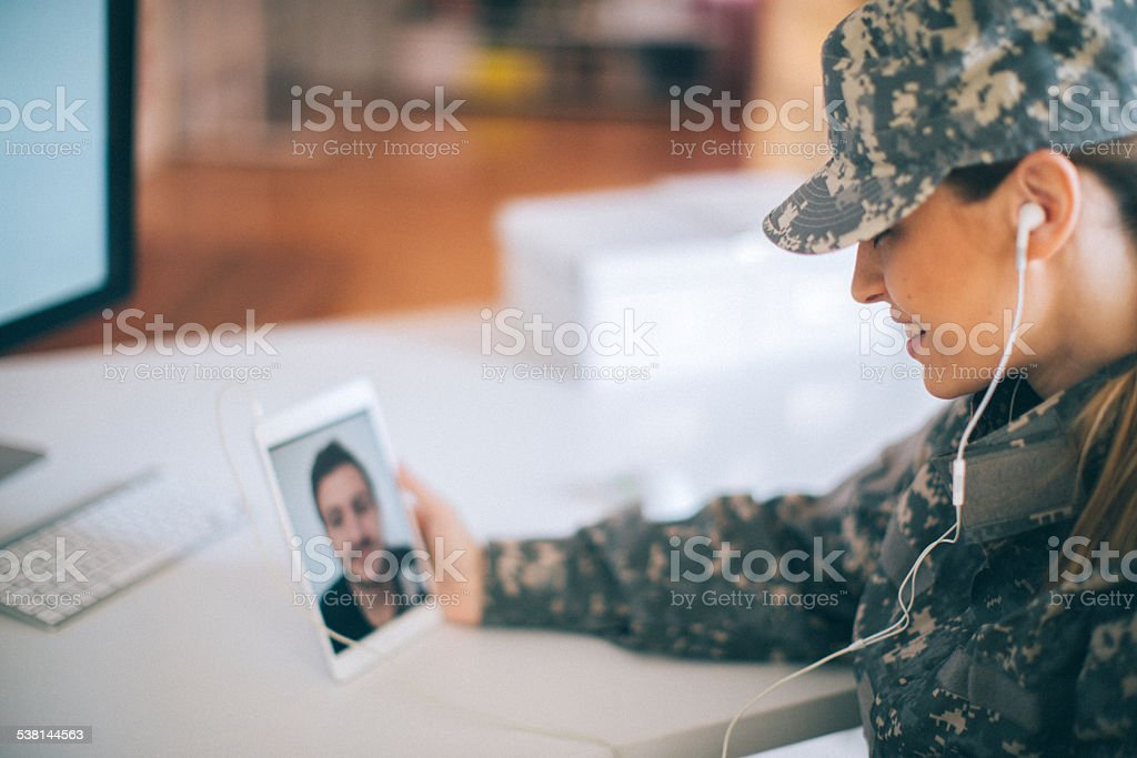 Woman soldier talking to her family stock photo