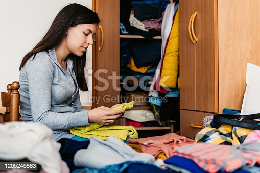 Young woman folding clothes and sorting it wardrobe.