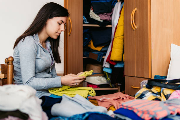 Woman sorting out wardrobe Young woman folding clothes and sorting it wardrobe. arrangement stock pictures, royalty-free photos & images