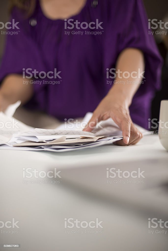 Woman sorts through monthly bills