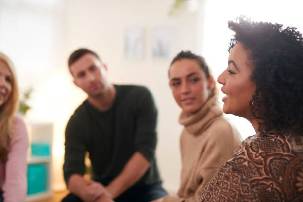 Woman Speaking At Support Group Meeting For Mental Health Or Dependency Issues In Community Space stock photo