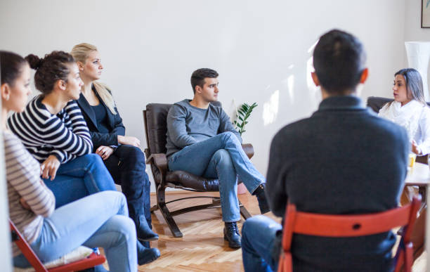 Woman speaking in group therapy session stock photo