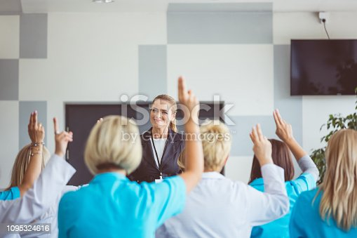 933450738 istock photo Woman speaking with medical staff voting on seminar 1095324616