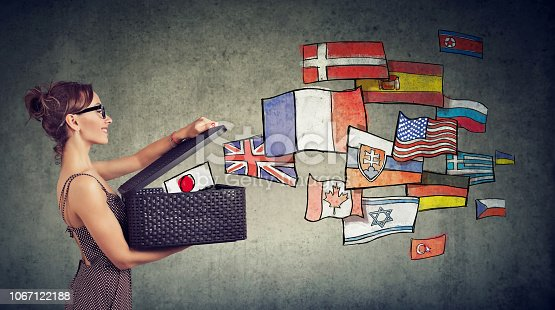 istock Woman speaks different languages opening a box with international flags flying away 1067122188