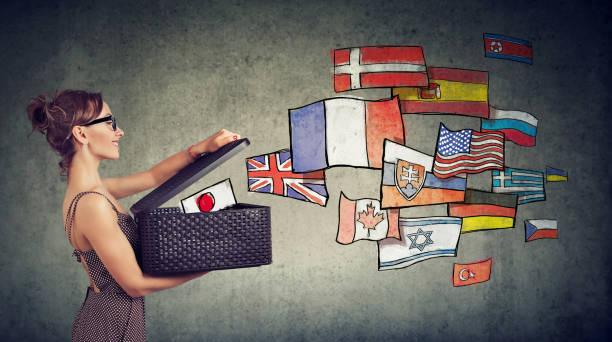 Woman speaks different languages opening a box with international flags flying away stock photo
