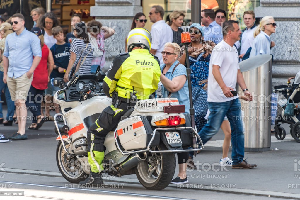 Woman speaks to a police man on a motorcycle stock photo