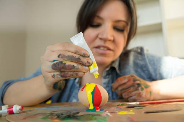 frau buchstabiert farbe über dem osterei - decoupage kunst stock-fotos und bilder