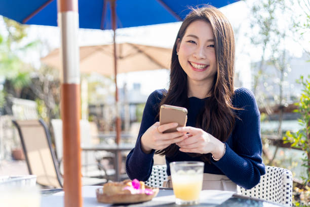 Woman Spending Holiday At Cafe On Open Terrace stock photo