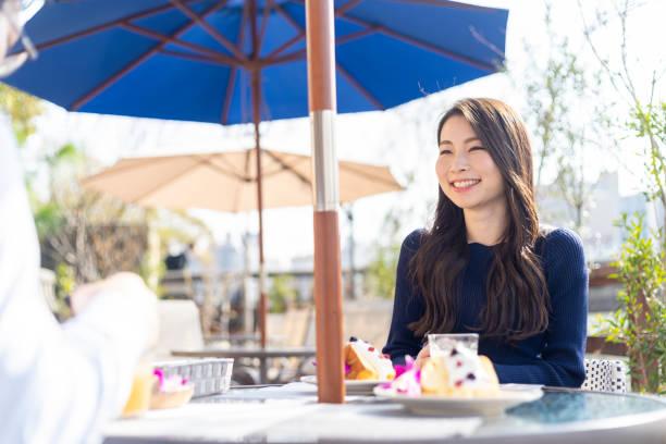 オープンテラスのカフェで女性を過ごす休日 ストックフォト