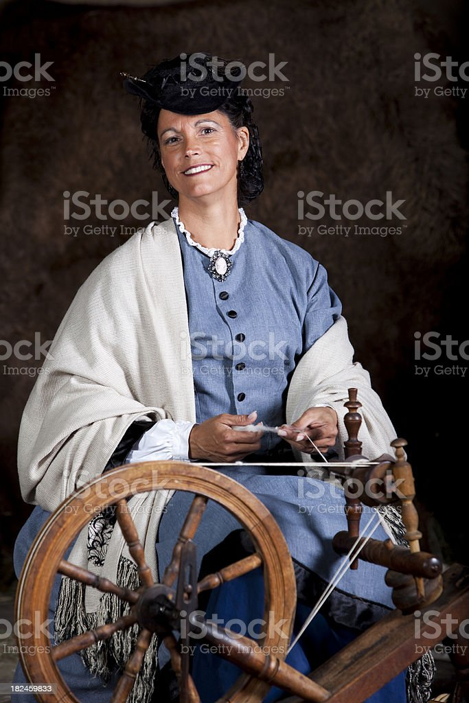 Woman spinning wool on antique spinning-wheel royalty-free stock photo