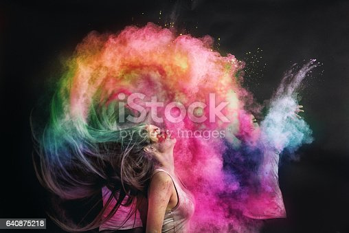 Woman splashing her hair with holi powder