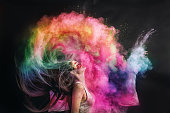 Woman splashing hair with holi powder