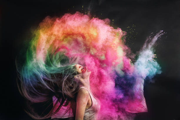 Woman splashing hair with holi powder stock photo