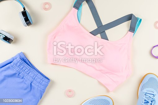 Woman sport clothes, sneakers, headphones and fitness tracker on neutral background. Sport fashion concept. Flat lay, top view