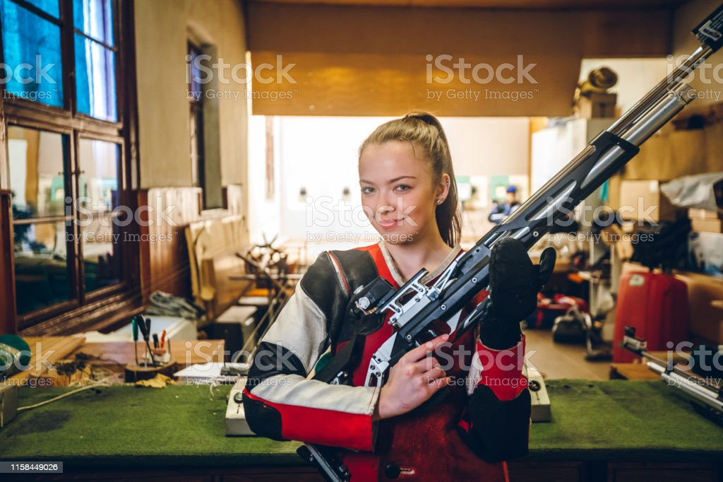 Young caucasian woman at sport shooter training.